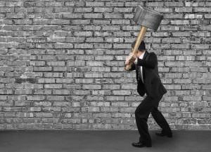 Using big hammer to crack old bricks wall